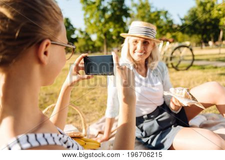 Joyful state of mind. Joyful teenager girl taking photos of her grandmother who is posing in front of her while enjoying a picnic together