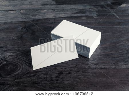 Photo of blank business cards on wood background. Mock-up for branding identity with plenty of copy space. Blank template for your design.