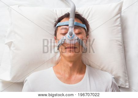 middle age asian man sleeping in his bed wearing CPAP headgear mask connected to air hose device for people with sleep apnea