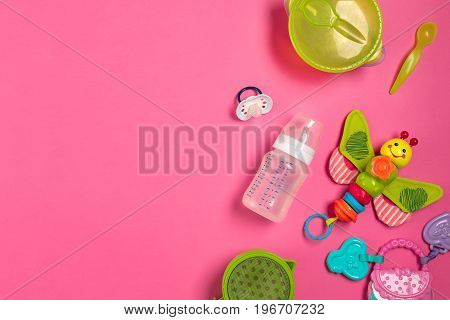 Baby toys and accessories on pink background. Top view. Copy space. Still life. Flat lay