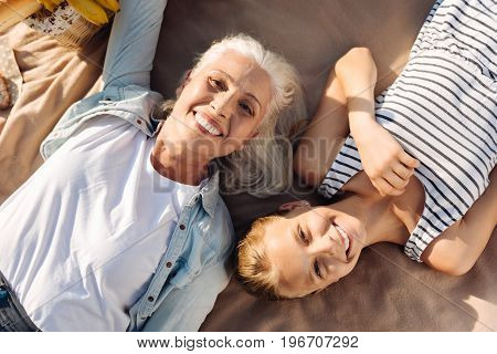 Positivity in mind. Top view of loving smiling senior woman lying on the blanket with her granddaughter while enjoying picnic together in the park