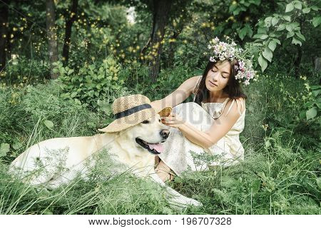 young woman and white labrador retriever dog in park
