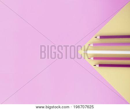 Colored pencils on pink and yellow background. Flat lay style with space for your text.