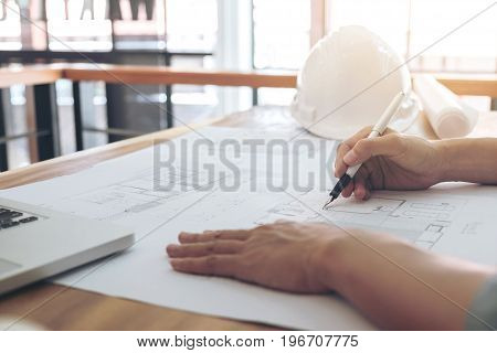 Image of engineer or architectural project Close up of Architects engineer's hands drawing plan on BluePrint with Engineering tools on workplace Construction concept.