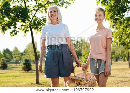 Happy life. Cheerful senior woman and her granddaughter carrying a picnic basket while resting in the park and expressing gladness