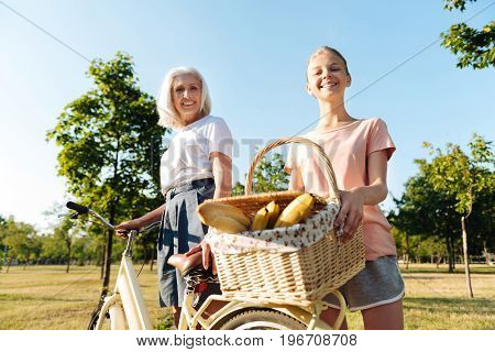 Ready to rest. Positive delighted teenager girl and her grandmother standing near bicycle and expressing joy while going to have a picnic