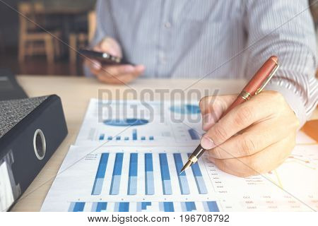 Business man or accountant working Financial investment Analyze business and market growth on financial document data graph and using phone to check stock price Accounting Economic commercial.