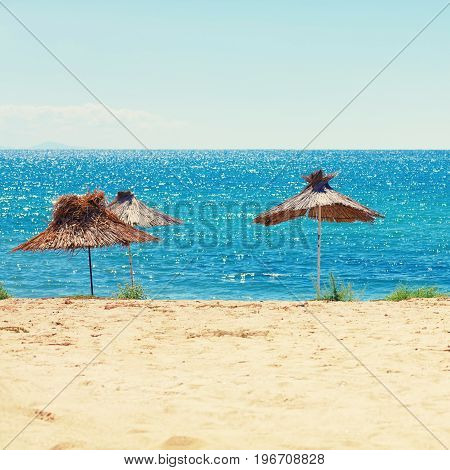 Straw beach umbrellas calm sea and clear sky. Beach on sunny day. Selective focus on the parasols. Toned image.