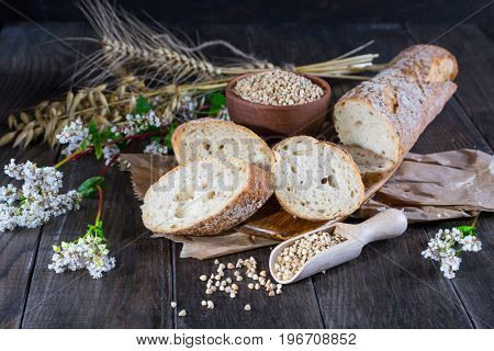 Bakery concept. Buckwheat bread, French baguette and stalks of whea, oats, buckwheat on dark wooden table.