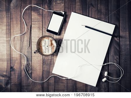 Blank stationery set on wood background. Paper letterhead coffee cup smartphone pencil and headphones. Paperwork template with plenty of copy space. Top view.