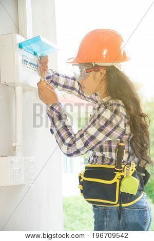 Asian female Electrician or Engineer check or Inspect Electrical System circuit Breaker on Power Distribution panel at home. poster