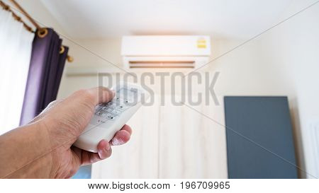 Hand holding the remote to control the air conditioner in the room.