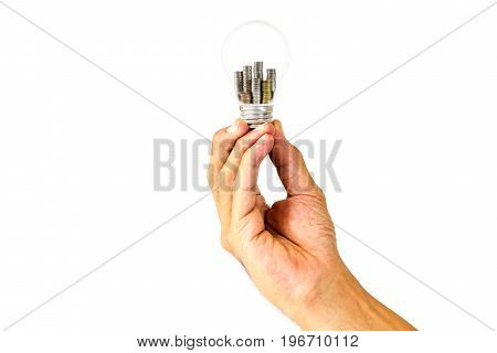 Man's hand holding a light bulb with stacks of coins inside on white background Concepts of business money saving and business growth.