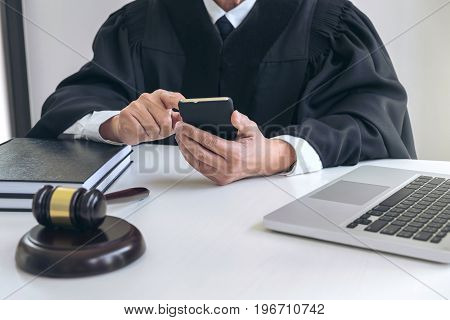 Male lawyer or judge working with smart phone and scales of justice Law book gavel report the case on table in modern office Law and justice concept.