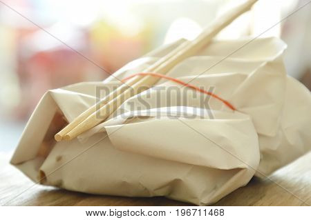 ready meal in paper packing by rubber band and wooden chopsticks