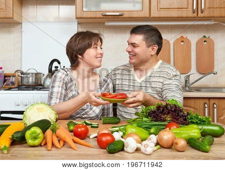 couple cooking in kitchen interior with fresh fruits and vegetables, healthy food concept, woman and man