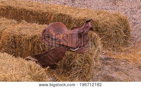 A leather cowboy saddle sitting on hay bale.