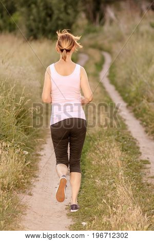 Young lady running on a rural road. Fitness woman running outdoors in nature. Running along country trail outdoor. Healthy active lifestyle.