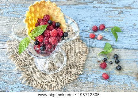 Fresh berries in glass bowl on wooden table