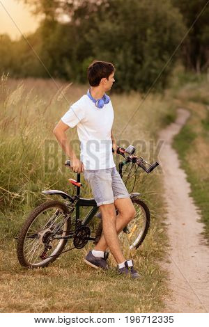 Attractive young guy with road bicycle outdoors. Guy wearing white T-shirt and jeans shorts with headphones on the neck. Cycling along country trail outdoor. Riding in the countryside. Healthy active lifestyle.