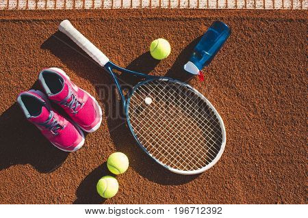 Tennis equipment and bottle of water on the clay court