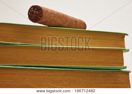 Cuban Brown Cigar Posed On A Stack Of Old Books