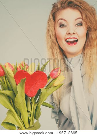 International womensm mothers or valentines day. Beautiful woman blonde hair fashion make up holding tulips bunch and red heart sign. Filtered image