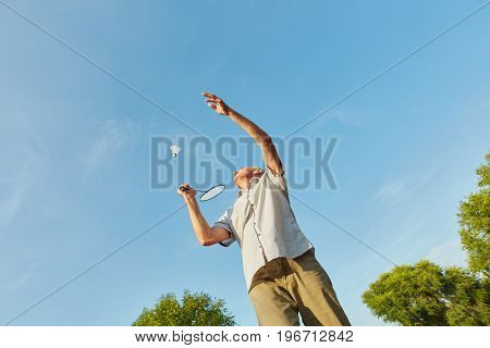 Old man making a service while playing badminton in summer