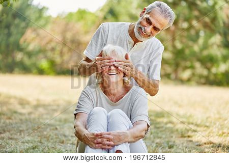 Senior covers his wife's eyes from the back in the nature
