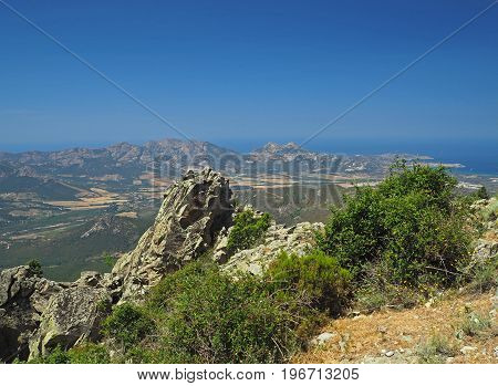 Sharp Stones Mountain Sea View With A Blue Sky And Green Bushes