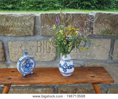 Demotic  White Blue Painted Pottery Flask And Vase With Field Flowers Ond Sandstone Wall Background