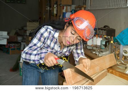 Pretty young Asian  woman using a hand saw to cut some wood in a wood shop.