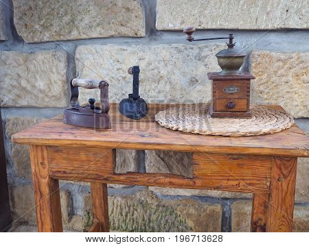 Two Old Rusty Antique Iron With Wooden Handle, Hand Coffee Grinder On Old Wooden Side Table With San