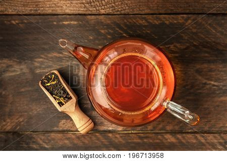 An overhead photo of a vibrant teapot with a scoop of loose tea leaves, on a dark rustic texture with a place for text. Selective focus