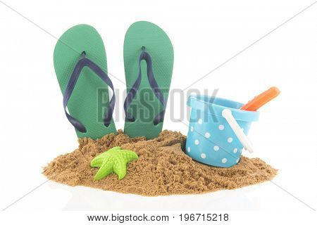 Green flip flops and toys in the sand at the beach