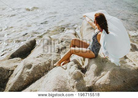 Pretty Yung Woman On The Stony Seaside Beach