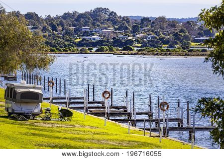 Typical Australian vacation - caravan camping and barbeque on grass near lake water and fishing boat