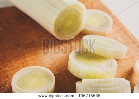 Cooking healthy food. Sliced and chopped leek closeup on wood background