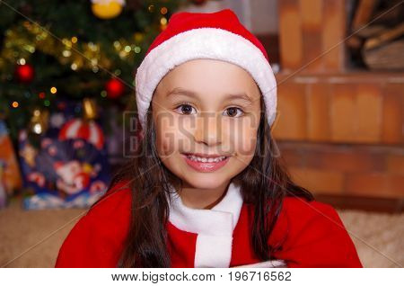 Beautiful smiling litle girl wearing a christmas clothes with a christmas tree background with some presents.