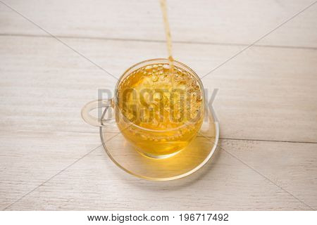 Pouring Tea. Cup Of Hot Tea And Tea Leaf On The Wooden Table