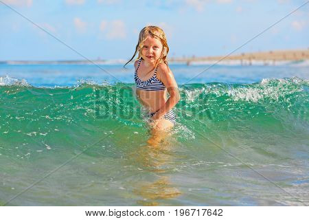 Happy family lifestyle. Baby girl splashing and jumping with fun in breaking waves. Summer travel water sport outdoor activities swimming lessons on tropical beach holiday with kids.