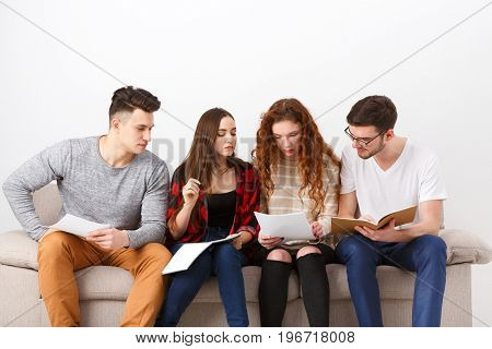 Diverse young students reading, preparing for exam, sitting on sofa in living room and studying, studio shot