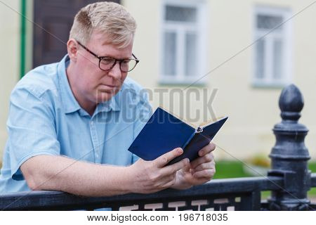 Man reading on street. Book in his hands.