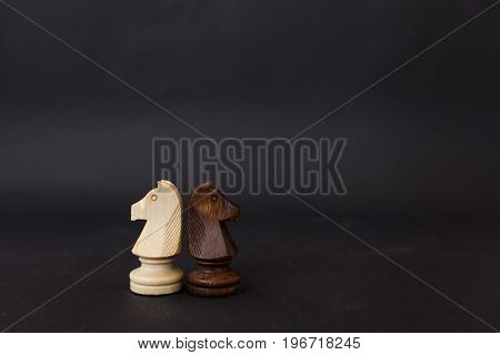 Wooden figures of a black and white horse. Chess pieces on a black background.