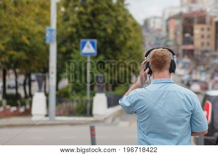Head in silhouette with headphones in city