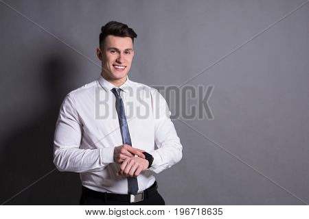 Confident youn businessman checking hand watch time on gray studio background, copyspace