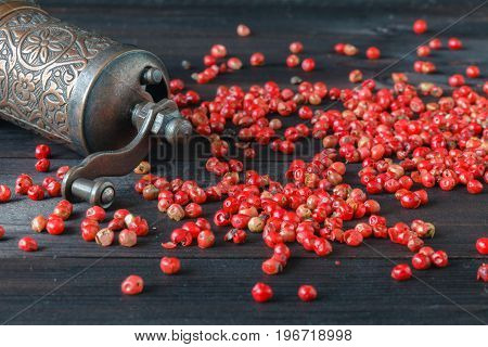 pink pepper and grinder on wooden table
