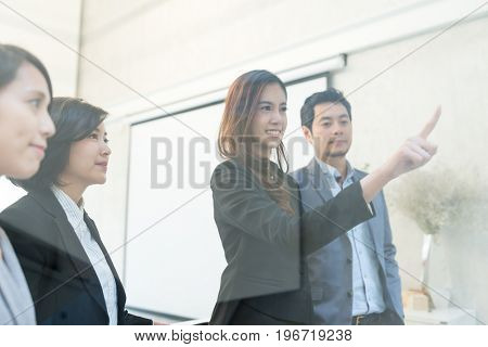 Business woman make a goal and pointing on glass of window