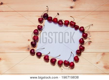 Card for notes with cherries berries on wooden background.