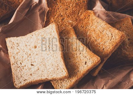 Toasted slices of white bread in craft paper on wooden table. Still life, food background, closeup
